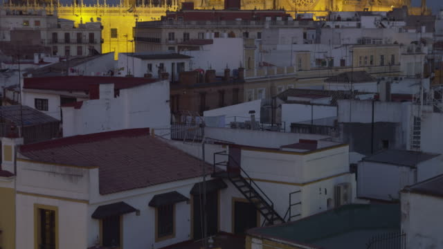 TU HA at dusk over rooftops of historic city center to cathedral (western façade) and La Giralda belltower