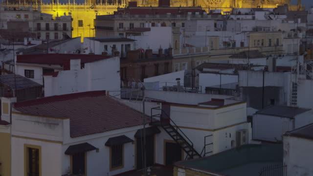 tu ha at dusk over rooftops of historic city center to cathedral (western faã§ade) and la giralda belltower - mar bildbanksvideor och videomaterial från bakom kulisserna