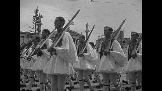 stockvideo's en b-roll-footage met at head of procession priests of greek orthodox church walk down both sides of street soldiers on sidewalks / soldiers march down street in formation... - aan elkaar bevestigd
