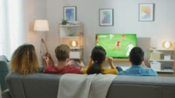 At Home Diverse Group of Sports Fans Sitting on a Couch Watching Important Soccer Match on TV, They Cheer for the Team, Celebrate Victory after Team Scoring Winning Goal. Cozy Room with Snacks and Drinks.