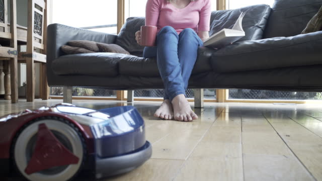 at home with a robot vacuum cleaner - cushion stock videos & royalty-free footage