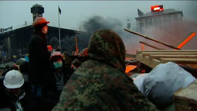 At least 26 dead following violent crackdown against protesters UKRAINE Kiev EXT Burntout vehicle and fires burning PAN protesters behind barricade...