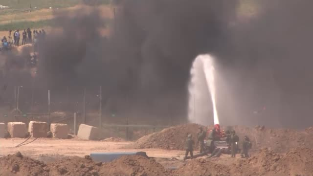 at least eight palestinians dead after protests along gaza's border with israel israel / gaza border wide shot of israeli soldiers firing water... - water cannon stock videos and b-roll footage