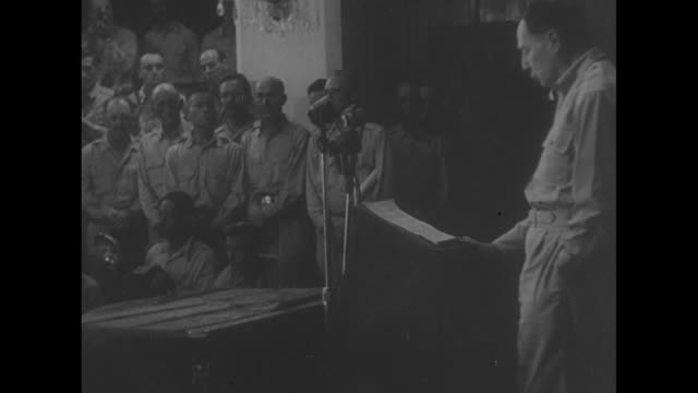At Manila's Malacanang Palace US military personnel listen as US Gen Douglas MacArthur continues reading his speech turning over the Filipino...