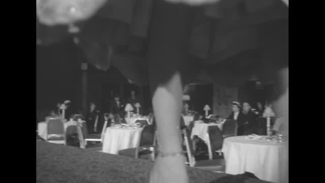 stockvideo's en b-roll-footage met at new york city's waldorf astoria, woman models beaded, cinched waist, spaghetti strapped, tea length, scalloped dress with jacket / woman models... - zoom out