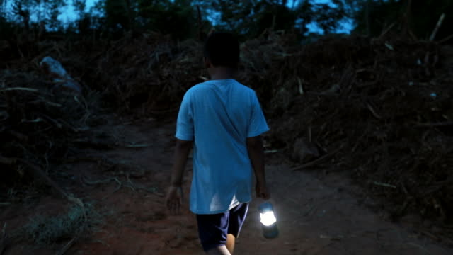 at night ,asian boy walking go to residential building after from natural disasters , slow motion - save the children stock videos & royalty-free footage
