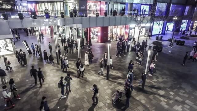 At night,lots of fashion young people walking at the Sanlitun Village shopping square, Beijing, China