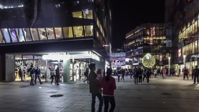 At night,the fashion young people walking at the Sanlitun Village shopping square, Beijing, China