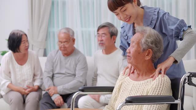 老人ホームでは、アジアの祖母や老人を助け、老人ホームを支援しながら、車椅子で座ってアジアの若い女性のホームケアに話しかけるアジアの先輩女性。 - 介護点の映像素材/bロール