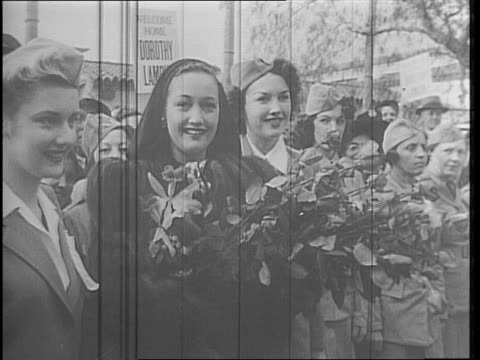 at paramount studios actress dorothy lamour moves through a crowd she has returned from a victory bond tour / soldiers stand with cameras to take her... - home guard britannica video stock e b–roll