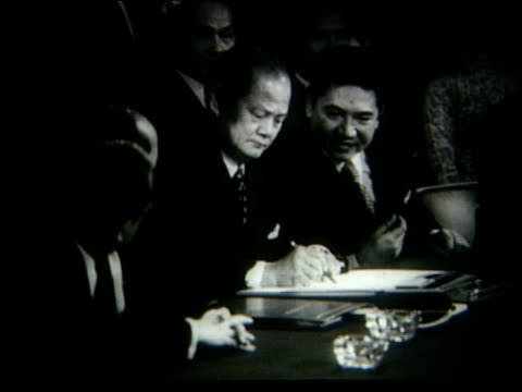 vídeos de stock, filmes e b-roll de at paris conference, dignitaries sign peace agreement between the us and north vietnam, william p rogers signing document / celebrations outside /... - 1973