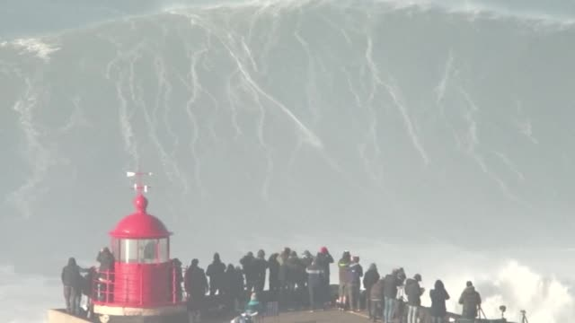 at portugal's nazare beach where thrill seekers come to catch some of the world's biggest waves an international community of extreme surfers ride... - biggest stock videos & royalty-free footage