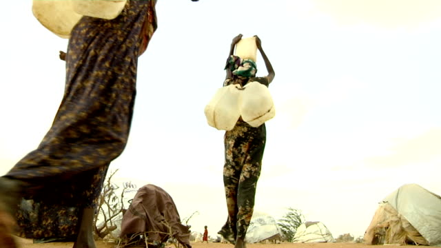 at refugee camp Women carrying water canisters on their heads on July 30 2011 in Dadaab Kenya