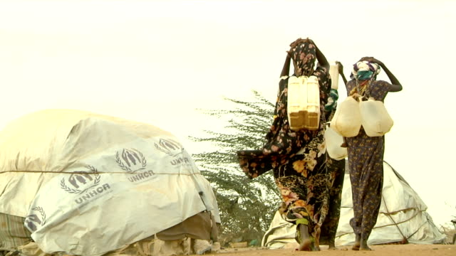 at refugee camp women carrying water canisters with their heads on july 30, 2011 in dadaab, kenya - carrying stock videos & royalty-free footage