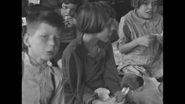 vidéos et rushes de at shelter, displaced women and children on cots; they were forced from their homes by the ohio river flood / children eat sandwiches / nurse strokes... - sandwich