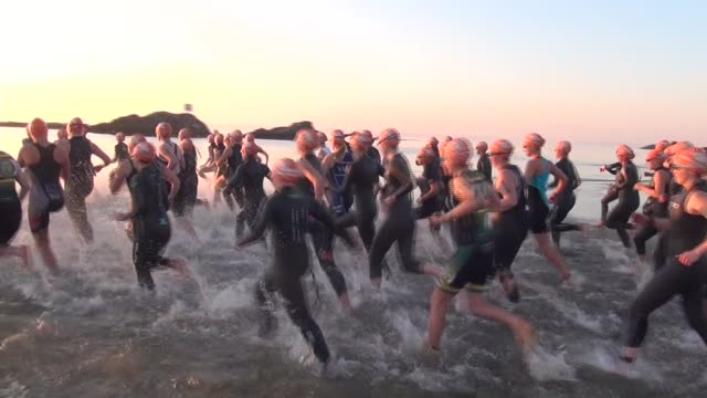 at sunrise female triathletes charge into long island sound for a one mile swim - salmini stock videos and b-roll footage