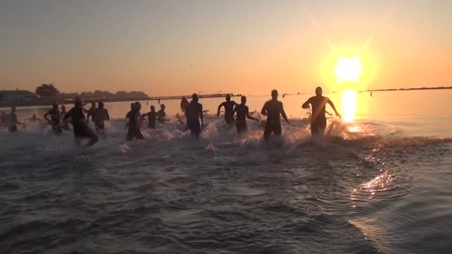 at sunrise male triathletes charge into long island sound for a one mile swim - salmini stock videos and b-roll footage