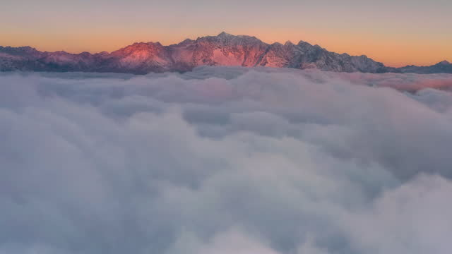 at sunrise, the sea of clouds rolling in front of the snow mountain is extremely spectacular - distant stock videos & royalty-free footage