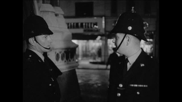vídeos de stock, filmes e b-roll de montage at ten o'clock, the british policeman ends his shift, handing over his beat to one of his colleagues / united kingdom 1950's - duas pessoas