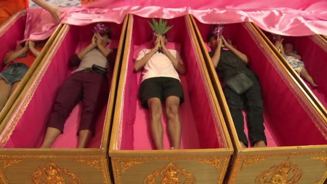 at thailands wat takien temple buddhist devotees undergo ritual resurrection lying down in coffins to cleanse themselves of bad karma - resurrection religion stock videos & royalty-free footage