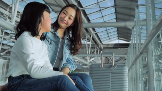 at the airport :mother and daughter looking out from big window at the airport.lifestyle,family,happiness,travel,journey,global,holidays concept.in the airport - east asian ethnicity video stock e b–roll