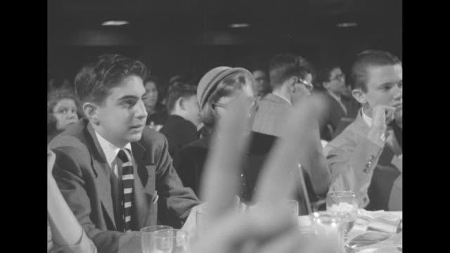 at the convention of the columbia scholastic press association, student journalists at table clap as man takes their photo / teen women at table,... - キャンペーンバッジ点の映像素材/bロール