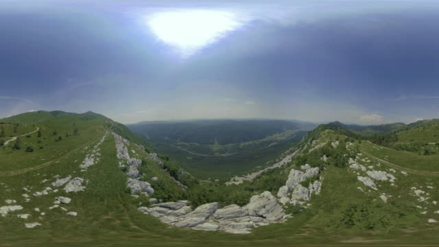 AERIAL VR 360: At the edge of a green mountain plateau overlooking a valley