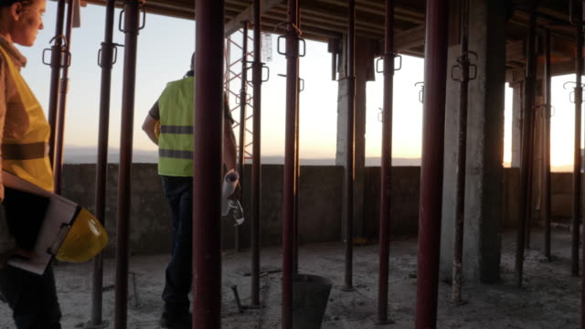 at the end of the day. meeting of a confident female architect and a construction worker discussing and working together at construction site of a residential building on a bright sunny day. - after work stock videos & royalty-free footage