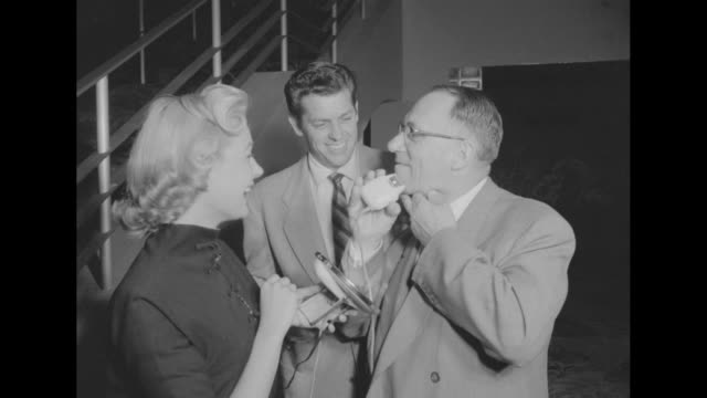 At the Paramount Theatre in Los Angeles actress Deedra Lawson holds a mirror for Jim Dankers as he shaves his face with an electric razor actor James...