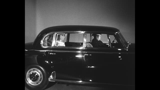At the Salon de automobile in the Grand Palais Parc des Exhibition / CU chauffeur drives Mercedes 300 B into room with a woman in an evening gown...