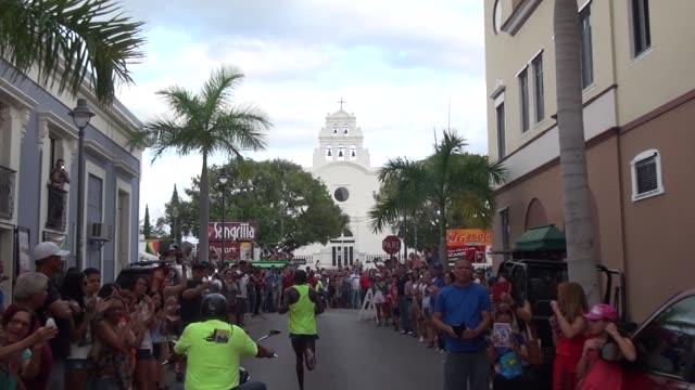 at the san blas halfmarathon in puerto rico elite runner leads the way through downtown coamo passing through massive crowds center of town crowds... - salmini 個影片檔及 b 捲影像