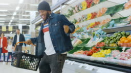 At the Supermarket: Happy Stylish Guy with Shopping Basket Dances Through Fresh Produce Section of the Store. Big Bright Shopping Mall with Customers Choosing Goods and Products.