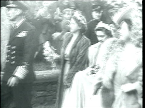 vídeos de stock, filmes e b-roll de at the wedding of patricia mountbatten and lord brabourne, spectators watch and drink tea in the cold as limousine arrives / lady mountbatten and... - 1946