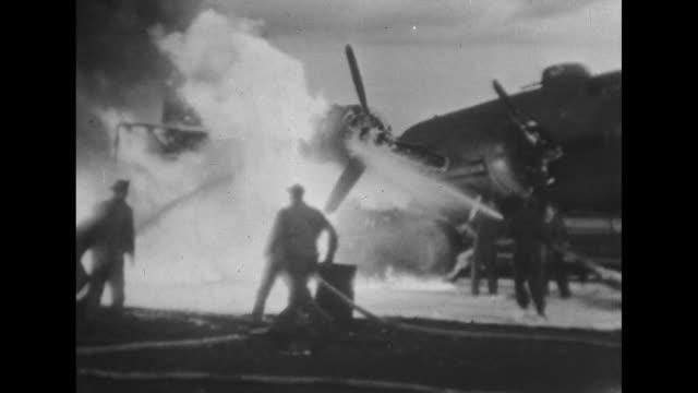 At twilight a B17 Flying Fortress plane burns with rising dark smoke men scramble to pour water onto the engine's flames / Fire from rises into the...