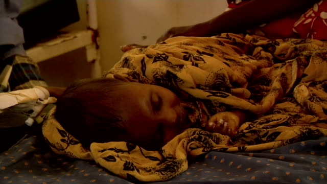 at UN hospital Doctor analyzes sick child lying next to mother on July 30 2011 in Dadaab Kenya
