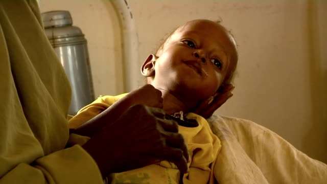at UN hospital Woman trying to give water to child on July 30 2011 in Dadaab Kenya