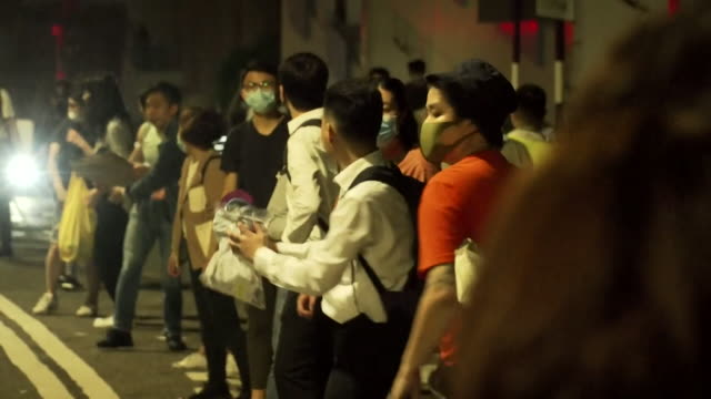 at university campus in hong kong students and protesters form human chain to supply frontline with water supplies and food - people in a line stock videos & royalty-free footage