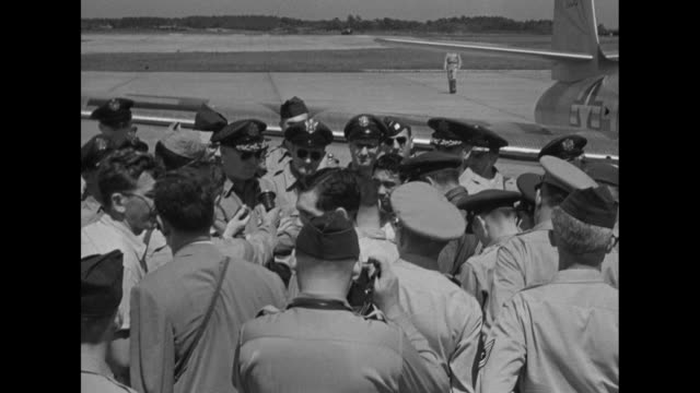 at yokota air base near tokyo during the korean war, two us officers, surrounded by journalists and other us air force personnel, talk about jet... - 軍事基地点の映像素材/bロール