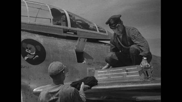 at yokota air base near tokyo us korean war pilot standing on wing of airplane removes component from side of plane while mechanic looks on / pilot... - united states airforce stock videos & royalty-free footage