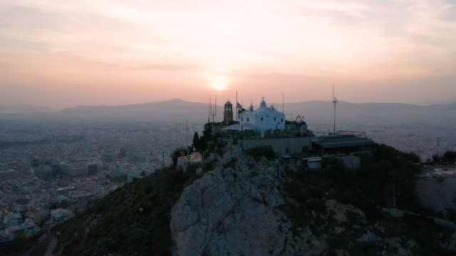 athens at sunset and lycabettus hill, the highest point in the city. aerial view. greece - lycabettus hill stock videos & royalty-free footage