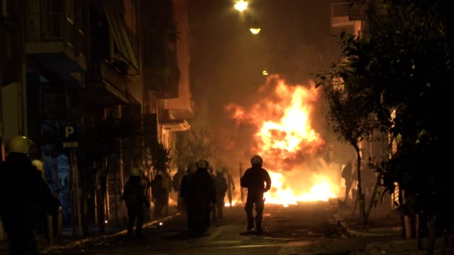 athens riot police run through flames caused by molotov cocktails, firecrackers and butane canister bombs during clashes following an anniversary... - 暴力点の映像素材/bロール