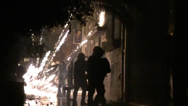 athens riot police run through flames caused by molotov cocktails firecrackers and butane canister bombs during clashes following an anniversary... - bombola video stock e b–roll