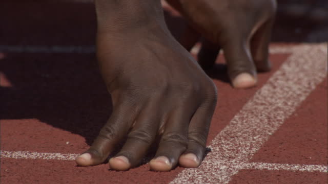 CU TU Athlete adjusting feet into track starting block and preparing for sprint / Sheffield, England, UK