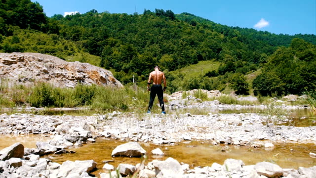 athlete admire his strengt near river - tracksuit bottoms stock videos & royalty-free footage