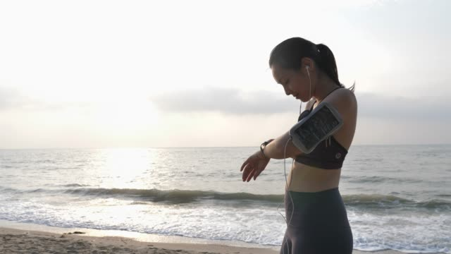 Athlete Asian woman Setting and checking smart watch before running on sandy beach sunrise in morning