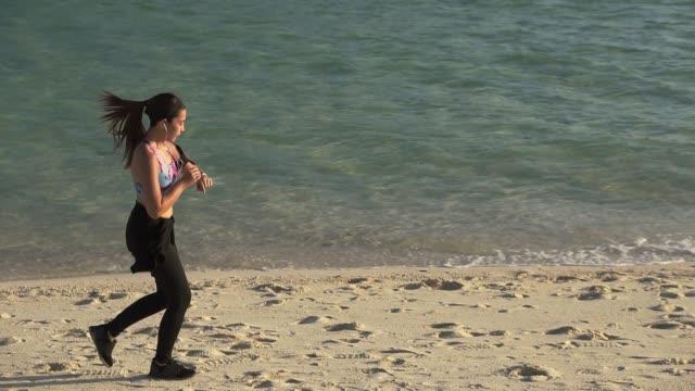 vídeos y material grabado en eventos de stock de atleta mujer asiática ajuste y comprobación de reloj inteligente corriendo en la playa de arena amanecer en la mañana - corredora de footing