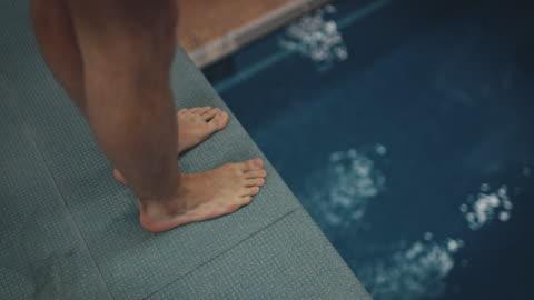 vídeos y material grabado en eventos de stock de atleta buceo de plataforma en piscina azul - alto descripción física