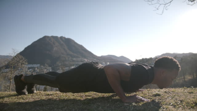 athlete does push ups on grass in park, view of mountains and lake behind - bodyweight training stock videos & royalty-free footage