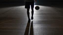 Athlete dribbling basketball on street at night