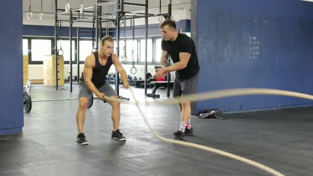 vídeos de stock e filmes b-roll de athlete exercising with ropes in gym - corda